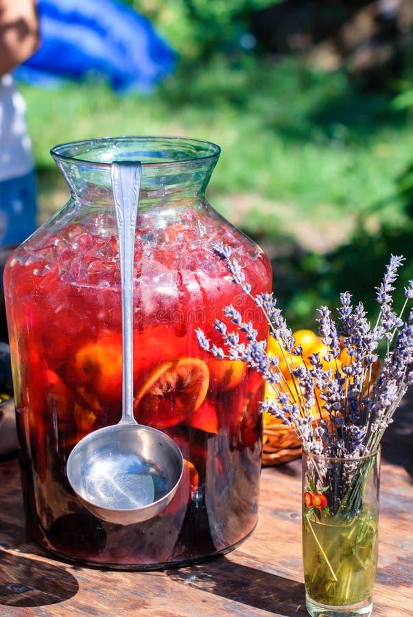 Una grande bottiglia di sangria fredda con una siviera sulla tavola della dacia fotografia stock