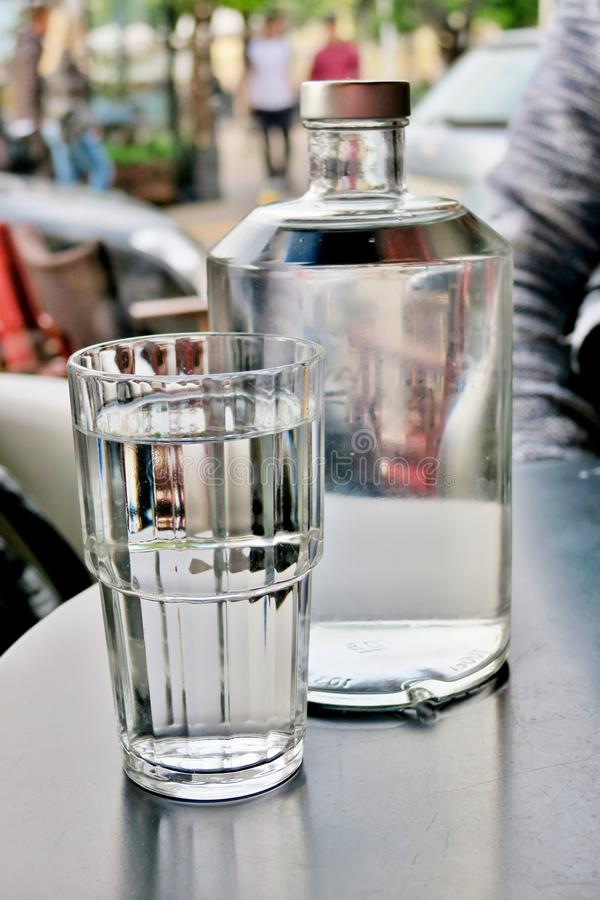 Una grande bottiglia trasparente di acqua con un seguente di vetro, primo piano immagini stock