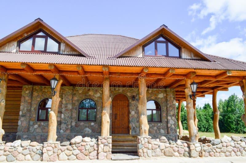 Una grande casa di legno della capanna nel legno dei ceppi delle plance e della pietra con le colonne dei tronchi di albero con u immagini stock