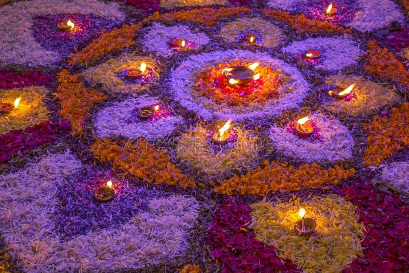 Una grande mandala dei petali variopinti del fiore fresco, con le candele brucianti alla notte sul festival di diwali fotografia stock