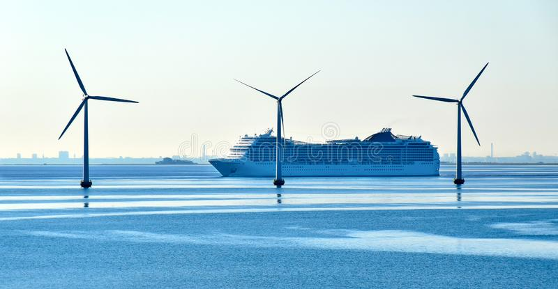 Una grande nave da crociera passa le turbine di vento di terra vicino al ponte di Oresund fra la Danimarca e la Svezia immagini stock