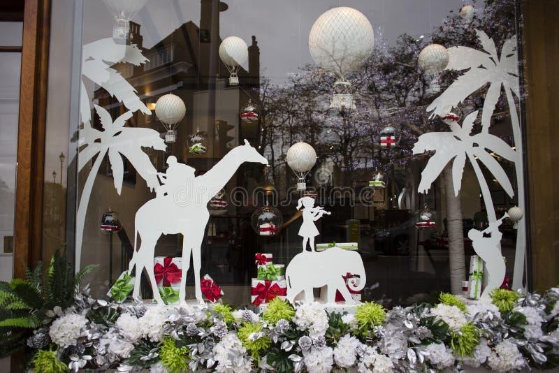 Una grande progettazione della finestra è stata osservata per le feste a Londra palloni, elefanti, giraffa, bambina e palme e Nat fotografia stock libera da diritti
