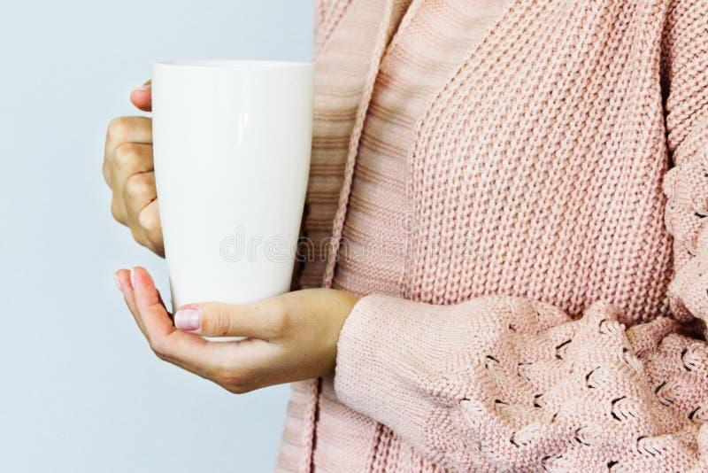 Una grande tazza bianca per caff? o t? nelle mani di una giovane donna vestita in un cardigan tricottato di colore della pesca immagini stock libere da diritti