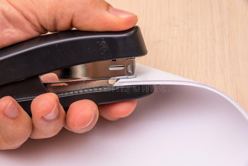 Una grapadora negra en su mano perfora muchas hojas de papel imagenes de archivo