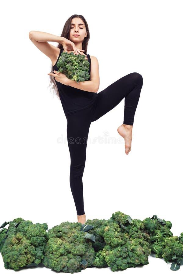 Una graziosa ragazza atletica tiene di fronte a lei una grande testa di broccoli freschi e pratica lo yoga immagini stock libere da diritti