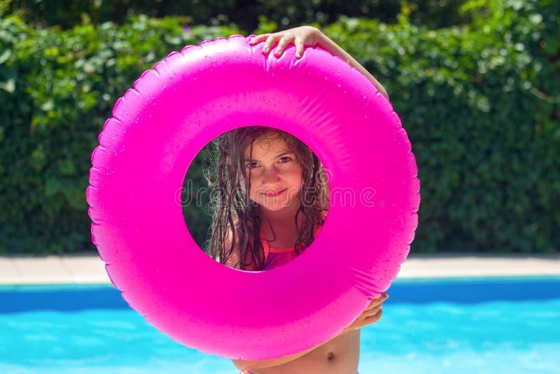 Una graziosa ragazzina che si diverte accanto al lato della piscina, giocando con la sua ghiera di nuoto, guardandola attraverso; fotografia stock libera da diritti