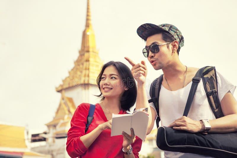 Una guía turística que se sostiene turística asiática más joven que se coloca en d que viaja fotos de archivo