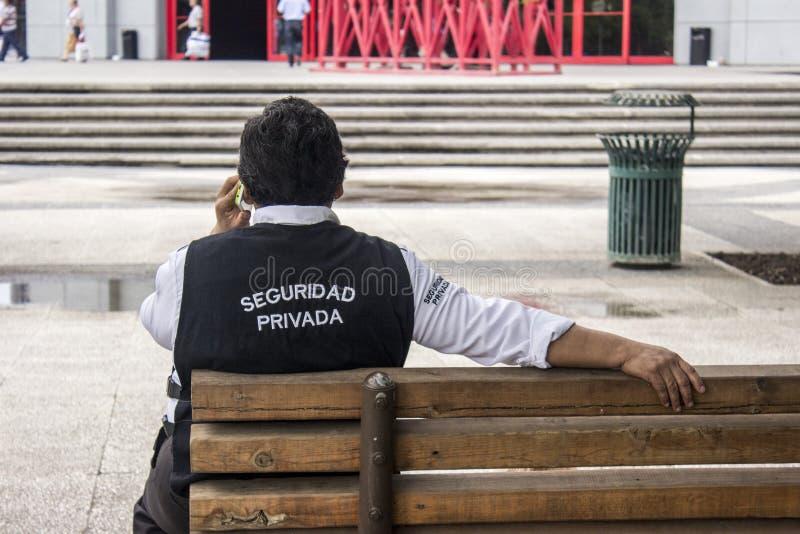 Una guardia giurata privata sitted in un banco in un parco che parla nel telefono immagini stock