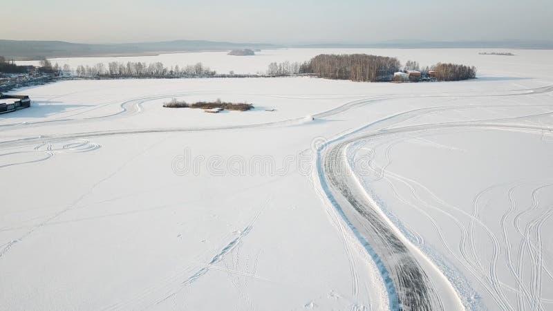 Una guida di veicoli attraverso la foresta di inverno sulla strada campestre Vista superiore dal fuco Vista aerea della strada in fotografie stock libere da diritti