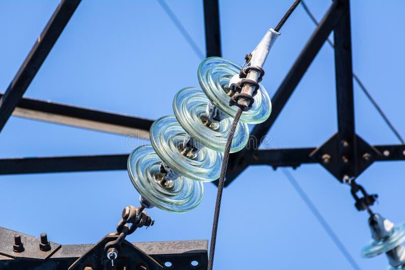 Una guirnalda de aisladores en los alambres eléctricos fotos de archivo