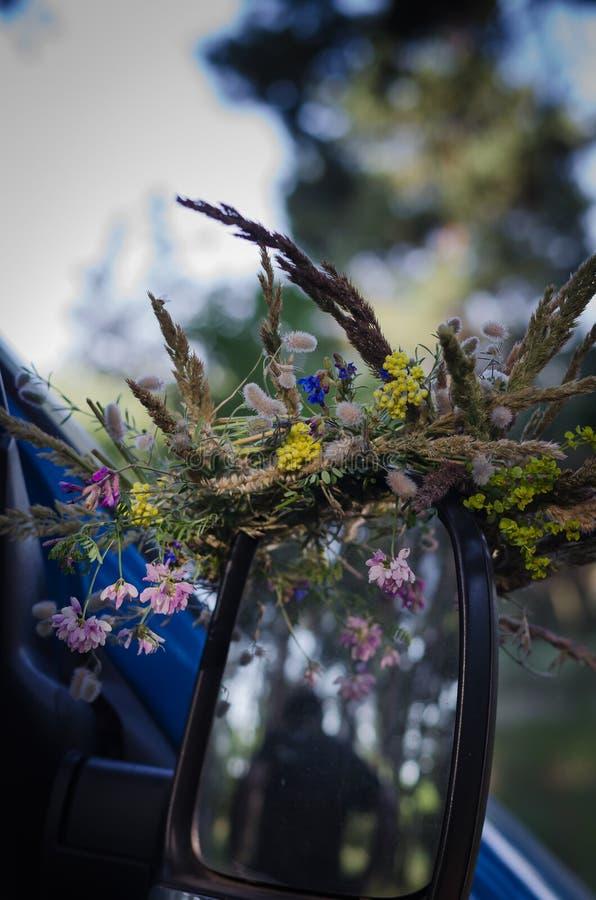 Una guirnalda de flores salvajes y de hierbas en el espejo retrovisor Preparación para el equinoccio eslavo del día de fiesta imagen de archivo
