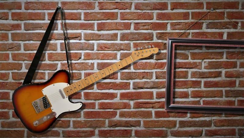 Una guitarra eléctrica está colgando en una pared de ladrillo fotos de archivo