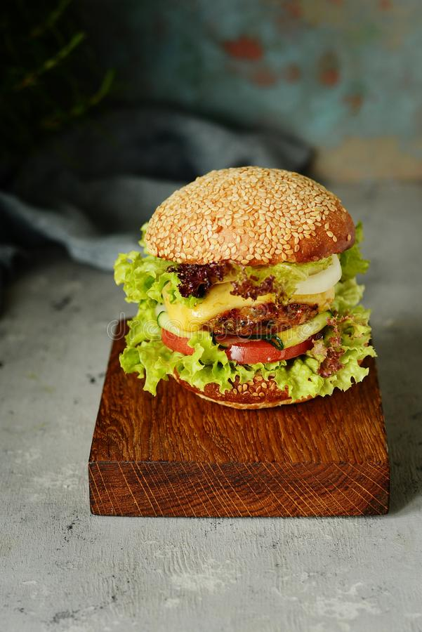 Una hamburguesa grande con una chuleta, verduras y un rollo fresco Bocadillo para los alimentos de preparación rápida del desayun foto de archivo