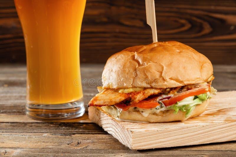 Una hamburguesa grande con el pollo cocinado en el carbón de leña Almuerzo con el vaso de cerveza en un fondo de madera El concep fotos de archivo