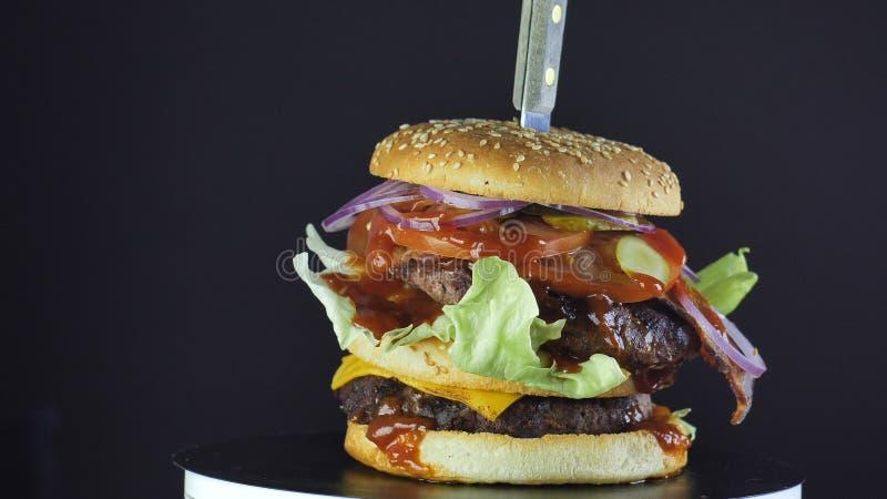 Una hamburguesa jugosa grande con un bollo asperjado con las semillas de sésamo con los verdes, los tomates y una chuleta doble,  fotos de archivo