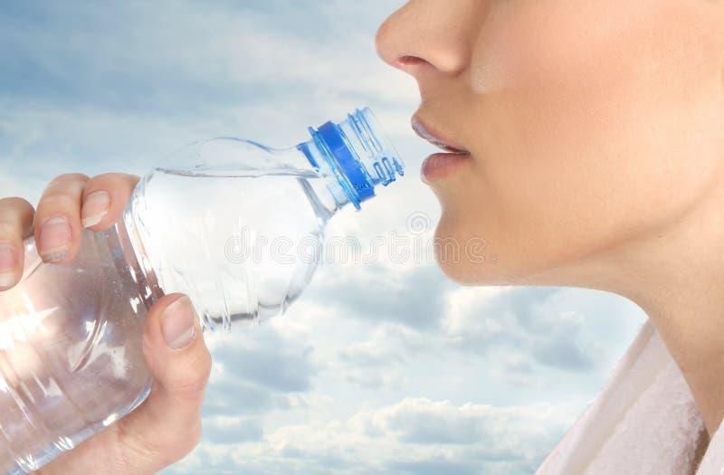 Una hembra joven está bebiendo el agua de restauración imágenes de archivo libres de regalías