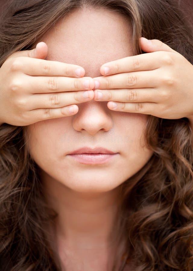 Una hermana más joven cerró ojos de su más vieja hermana por las manos imagenes de archivo