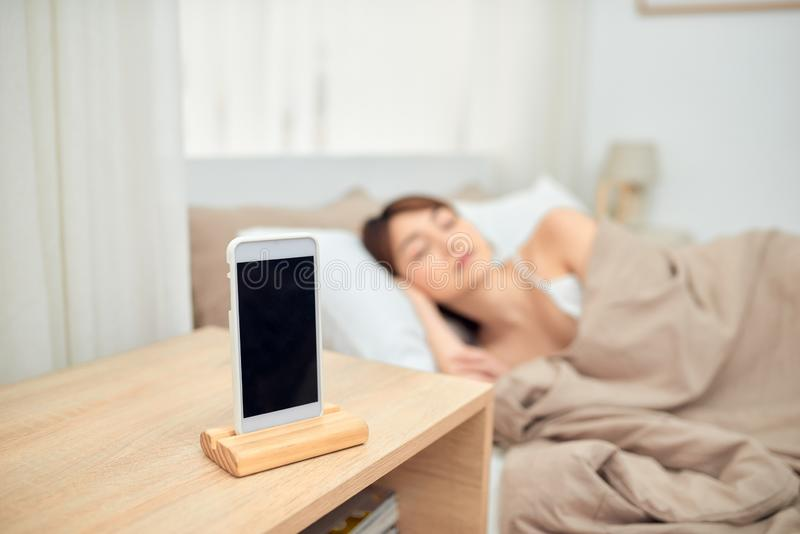 Una hermosa joven tendida en la cama cómoda y alegremente con teléfono móvil para alarmar imagenes de archivo