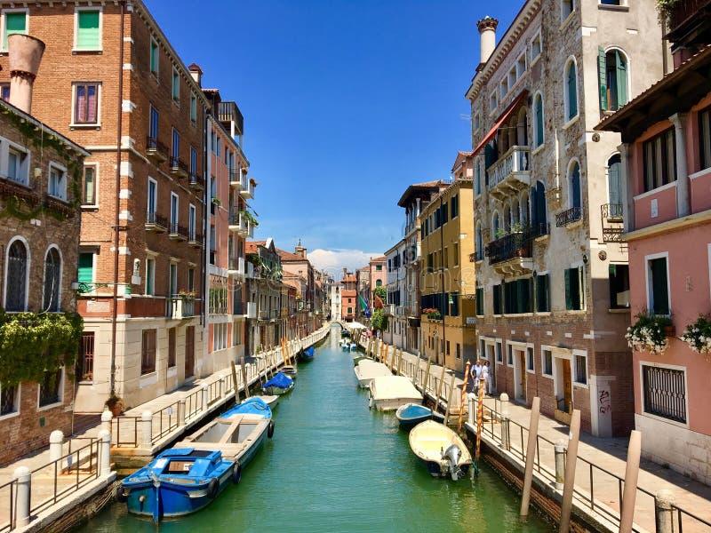 Una hermosa vista increíble de un canal en Venecia, Italia en un día de verano brillante El canal se alinea con los barcos y colo imagen de archivo