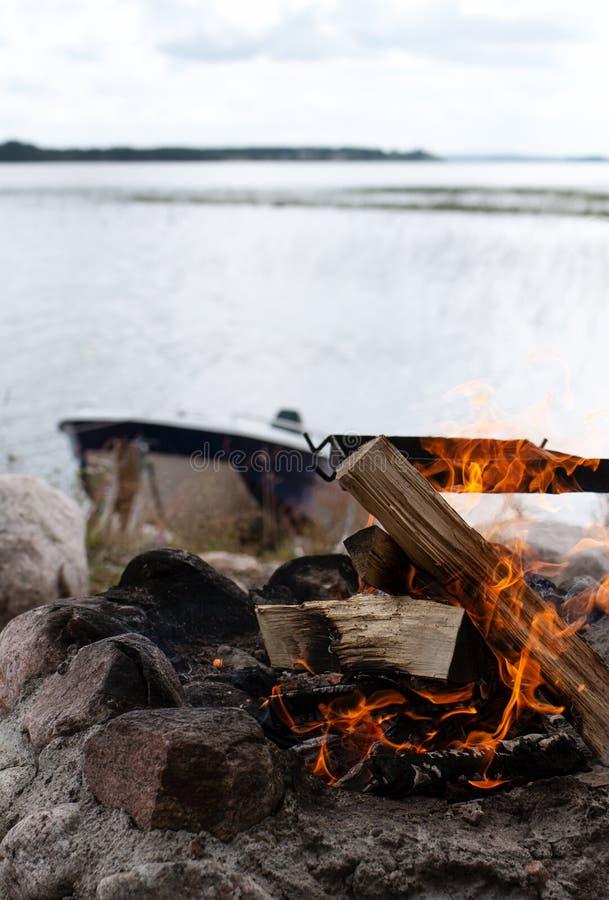 Una hoguera chispeante al lado de un barco y de un lago - opinión nórdica del verano imagen de archivo libre de regalías