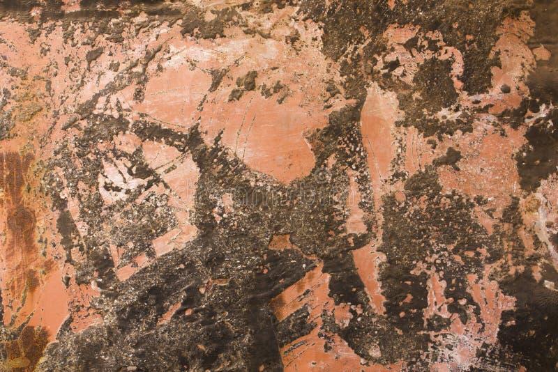 Una hoja de metal rosada roja sucia vieja con los rasguños y la textura negra de la superficie áspera de las manchas y del moho d imagen de archivo libre de regalías