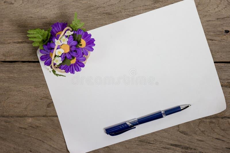 Una hoja de papel con una pluma en el escritorio de oficina de madera foto de archivo libre de regalías