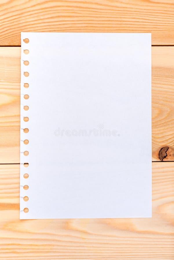 Una hoja de papel en los tableros de madera fotos de archivo