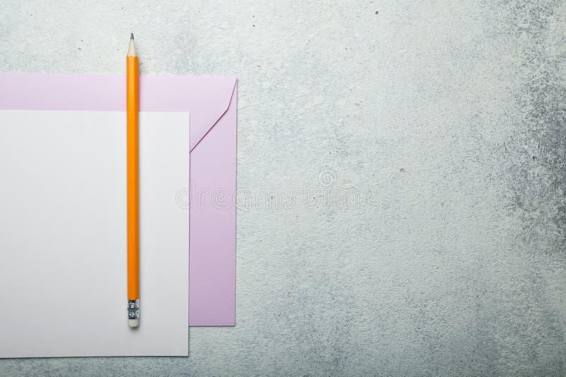 Una hoja de papel, un sobre rosado y un lápiz Tarjeta del día de San Valentín del amor en un fondo blanco del vintage Copie el es foto de archivo libre de regalías
