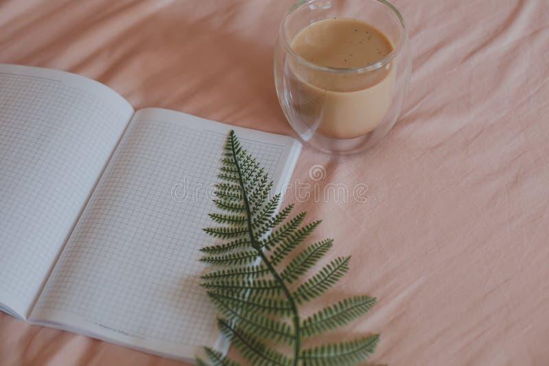 Una hoja del helecho, de un cuaderno limpio y de una taza de café por la mañana en cama imagenes de archivo