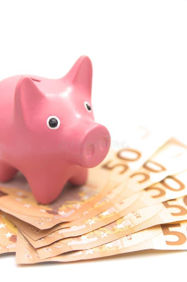 Una hucha cerdo-formada rosada en una buena cantidad de cuentas euro foto de archivo