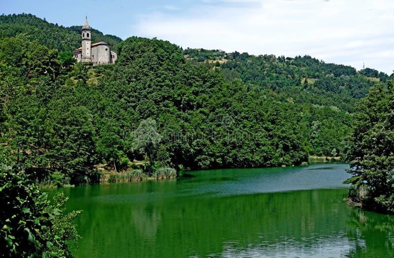 Una iglesia con su campanario en el lago del ` Alpi del dell de Castel foto de archivo