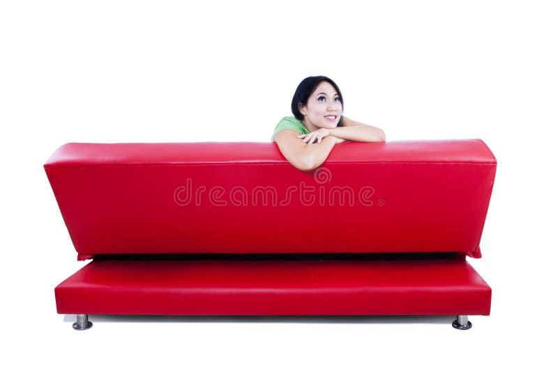 Una imagen aislada del sofá rojo con la hembra pensativa