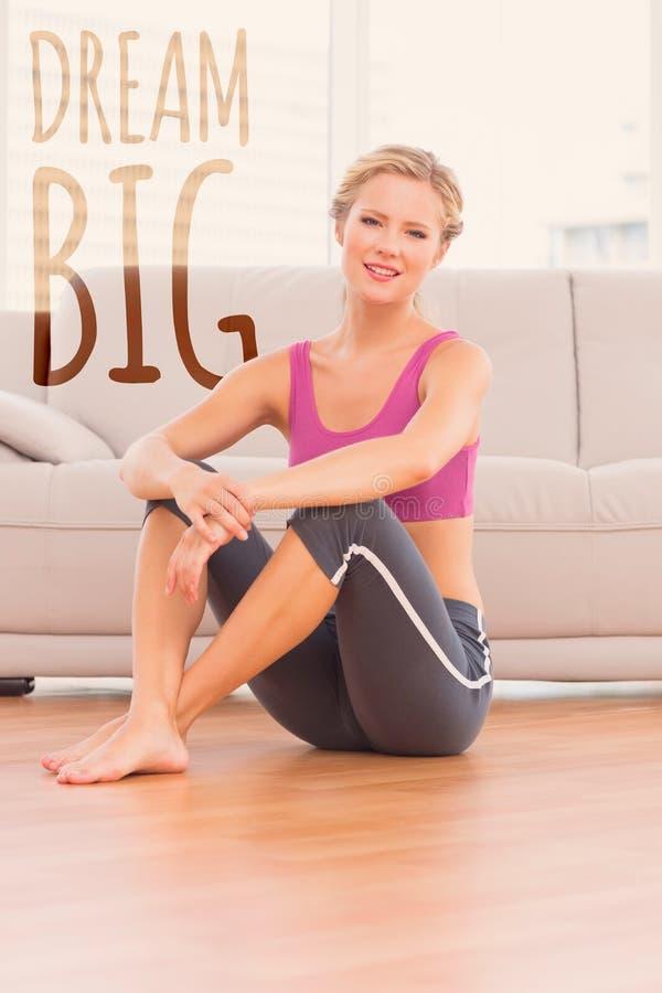 Una imagen compuesta de la sentada rubia atlética en el piso que sonríe en la cámara imagen de archivo
