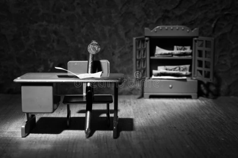 Una imagen conceptual de un clavo del hierro que se sienta detrás de un escritorio para tachonar imagenes de archivo