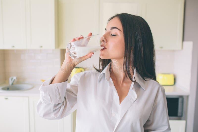 Una imagen de la muchacha del gorgeus que se coloca en cocina y leche de consumo de la taza de cristal Ella está manteniendo ojos fotos de archivo libres de regalías