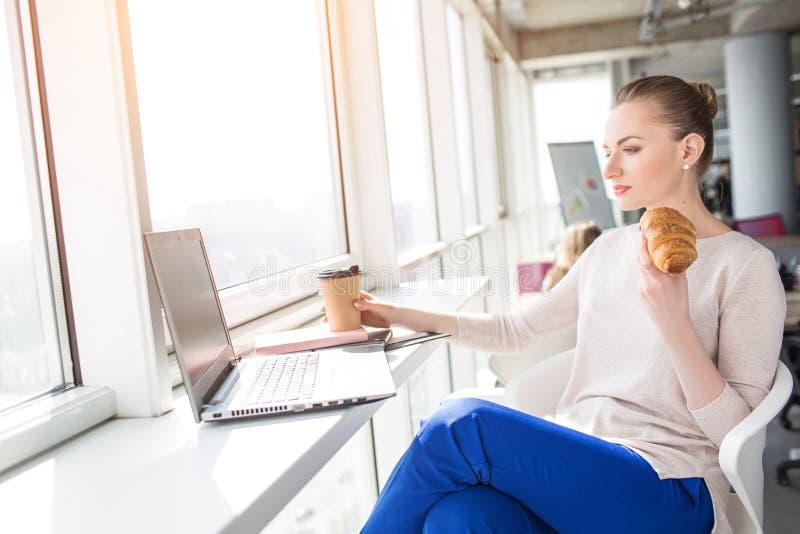 Una imagen de la mujer que almuerza en el trabajo Ella está comiendo un croissan y tiene una taza de café en la tabla También la  fotos de archivo libres de regalías