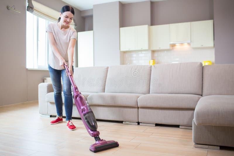 Una imagen de la mujer se coloca en el apartamento-estudio y la limpieza del piso Ella utiliza el aspirador para ése La muchacha  imágenes de archivo libres de regalías