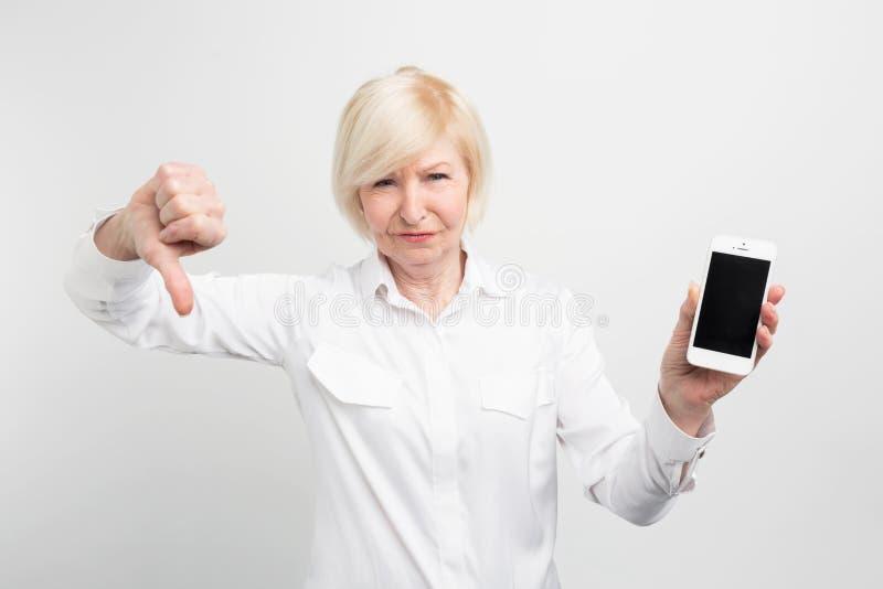 Una imagen de la señora madura con nuevo smartphone Ella lo ha probado y admitido este teléfono es mún Ese ` s porqué ella foto de archivo