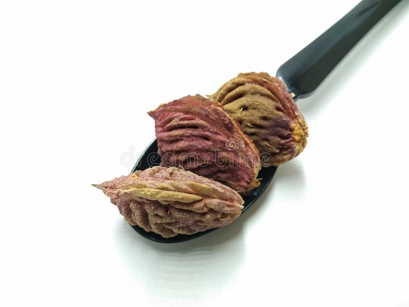 Una imagen de la semilla del melocotón en la cuchara negra, fotos de archivo
