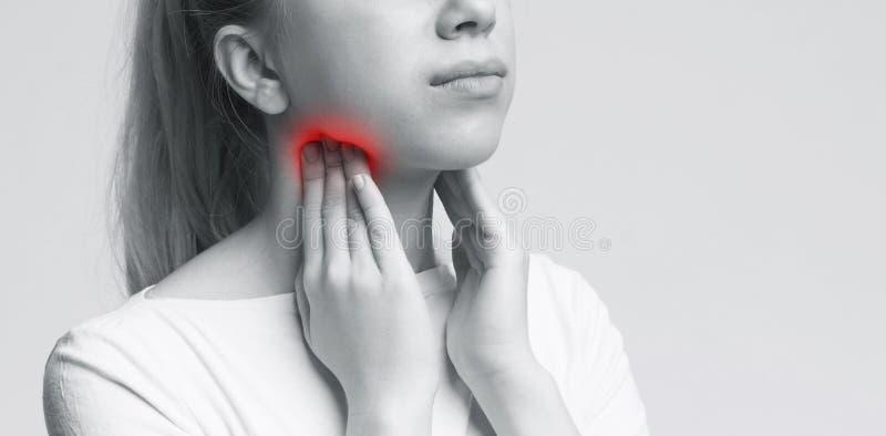 Una imagen de una mujer joven que sufre de tonsillities sobre el fondo blanco fotos de archivo libres de regalías