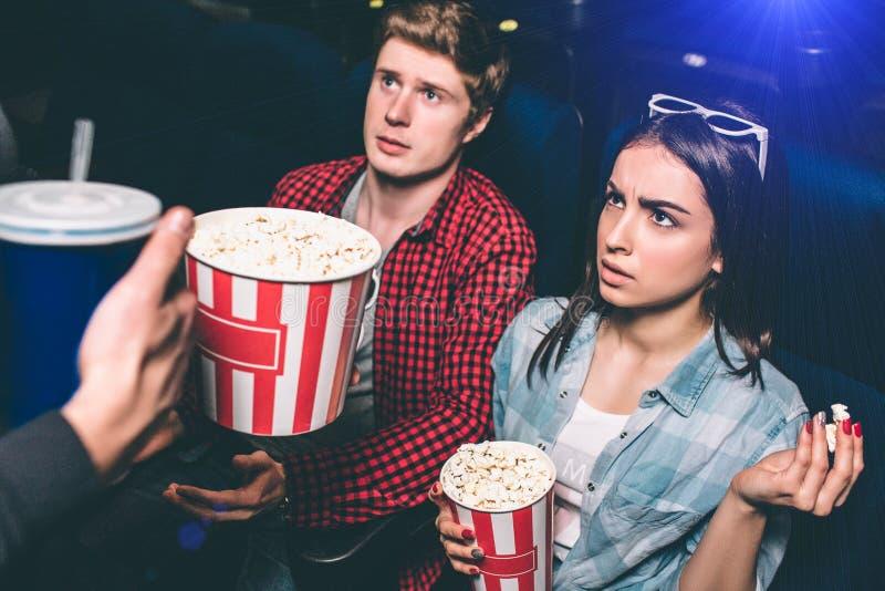 Una imagen de pares jovenes infelices y no satisfechos Están mirando para servir que los distraen de película de observación imágenes de archivo libres de regalías