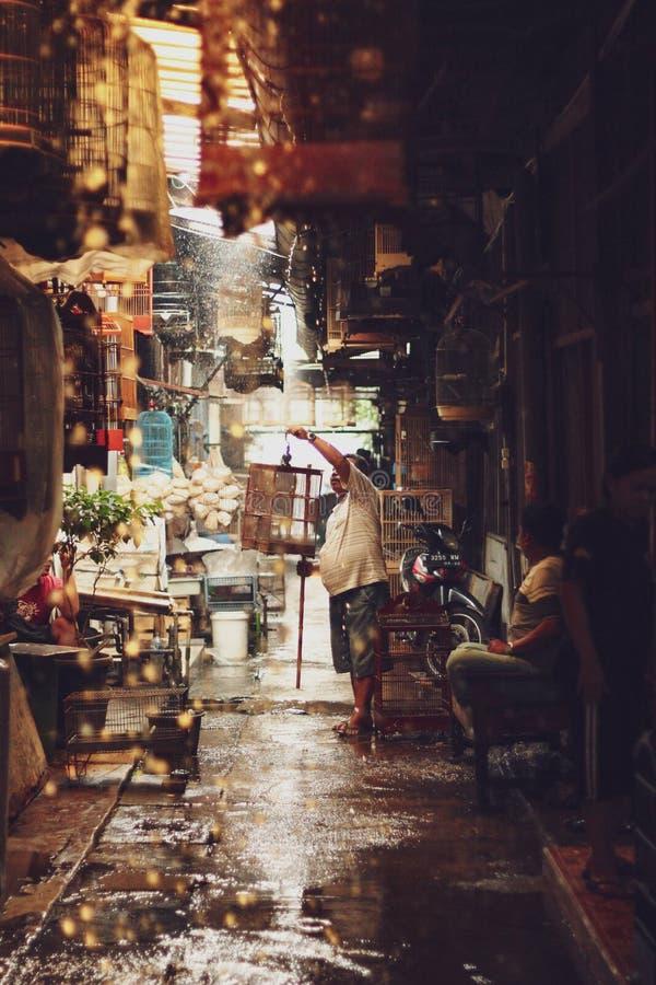 Una imagen de un hombre vende pájaros aquí en mercado local de la multitud foto de archivo