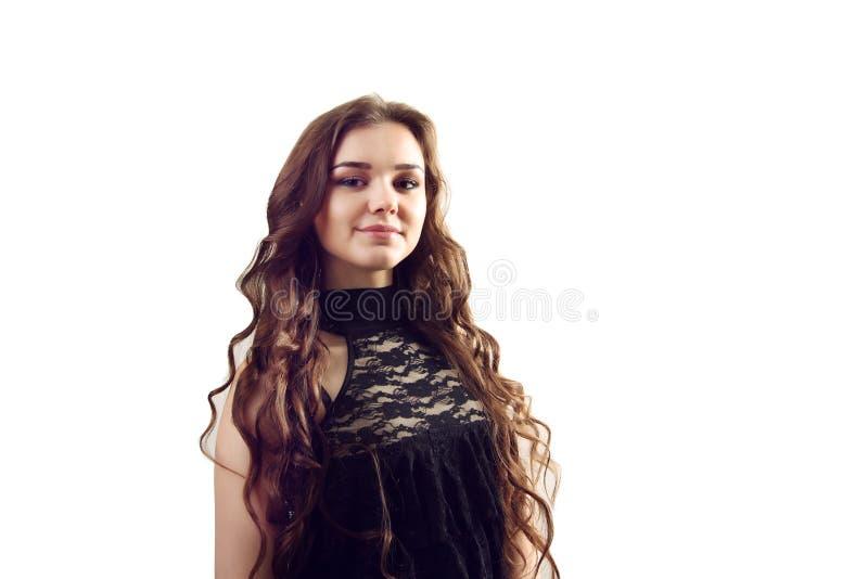 Una imagen de una mujer hermosa joven en un vestido negro que plantea el ove imagen de archivo libre de regalías