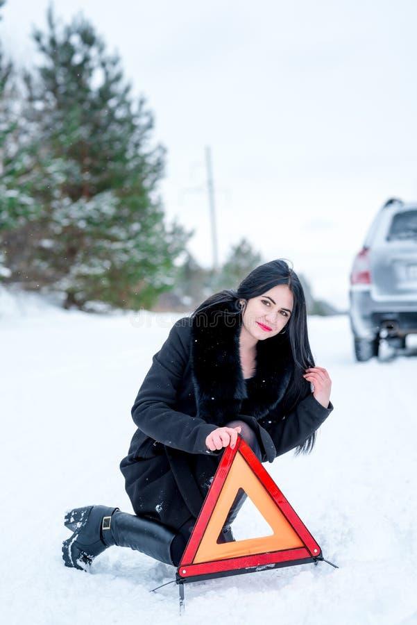 Una imagen de una mujer joven que tiene un problema con un coche en un wint imagen de archivo
