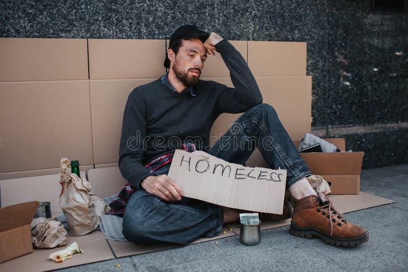 Una imagen del hombre que se sienta en la tierra y que sostiene carboard sin hogar en sus manos Él está triste y cansado El indiv imagen de archivo