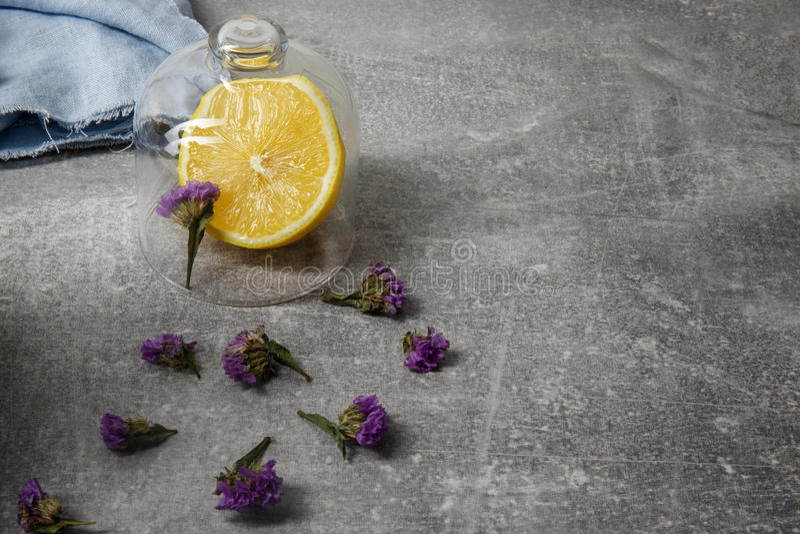 Una imagen del primer de una composición hermosa en un fondo gris Limón brillante, tela azul y pétalos secados de la púrpura fotografía de archivo libre de regalías