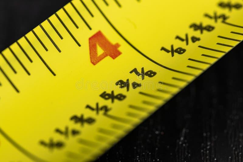 Una imagen macra de una cinta métrica amarilla imagen de archivo
