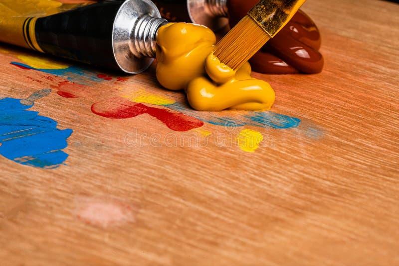 Una imagen macra de las pinturas acrílicas del artista exprimió sobre una paleta de madera para pintar imagen de archivo libre de regalías