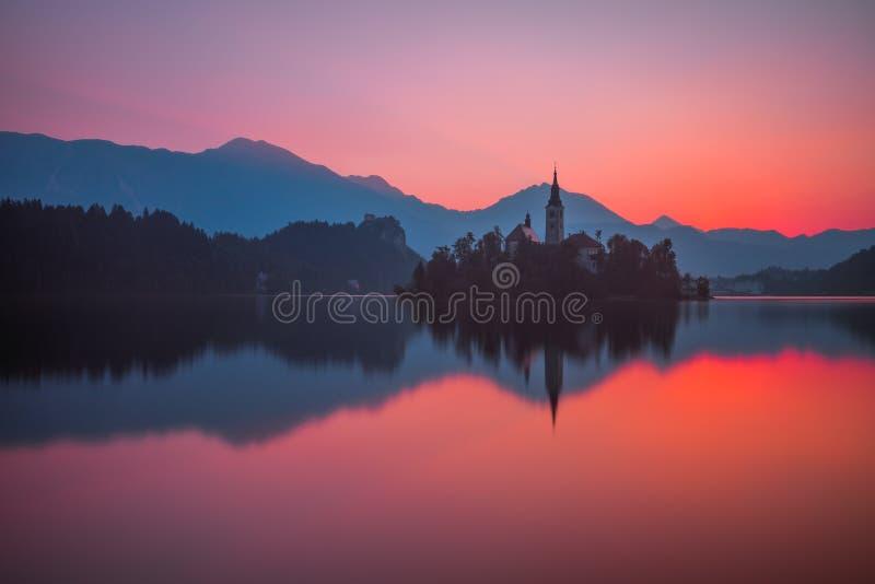 Una isla con la iglesia en el lago sangrado, Eslovenia en la salida del sol fotografía de archivo