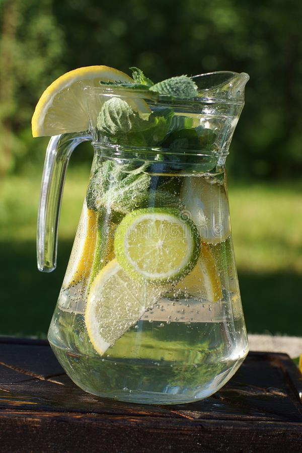 Una jarra con una limonada fría en un día de verano caliente en un flotador del claro, del limón, de la cal y de la menta dentro imágenes de archivo libres de regalías